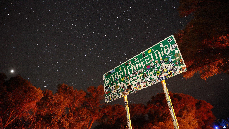 """Ein mit Aufklebern überklebtes Schild mit der Aufschrift """"Extraterrestrial Highway"""" steht nachts unter einem Sternenhimmel."""