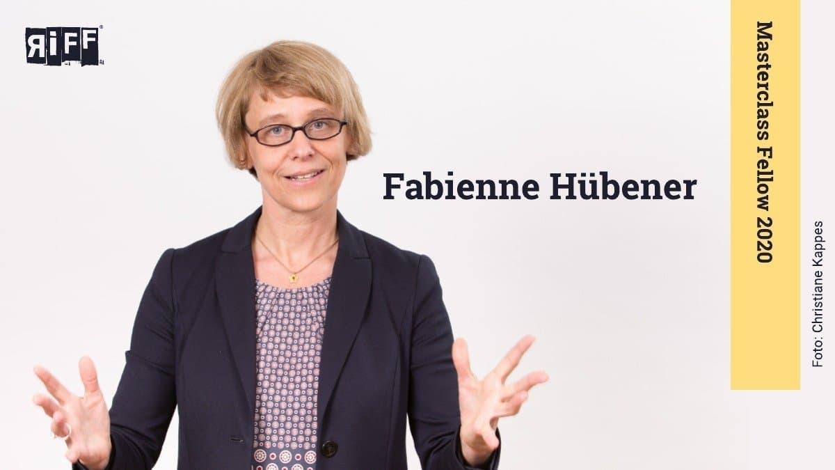 """Eine blonde Frau mit Brille schaut in die Kamera und breitet ihre Arme nach vorne aus. Rechts neben ihr steht der Name Fabienne Hübener. Daneben befindet sich ein Banner mit der Aufschrift """"Masterclass Fellow 2020""""."""