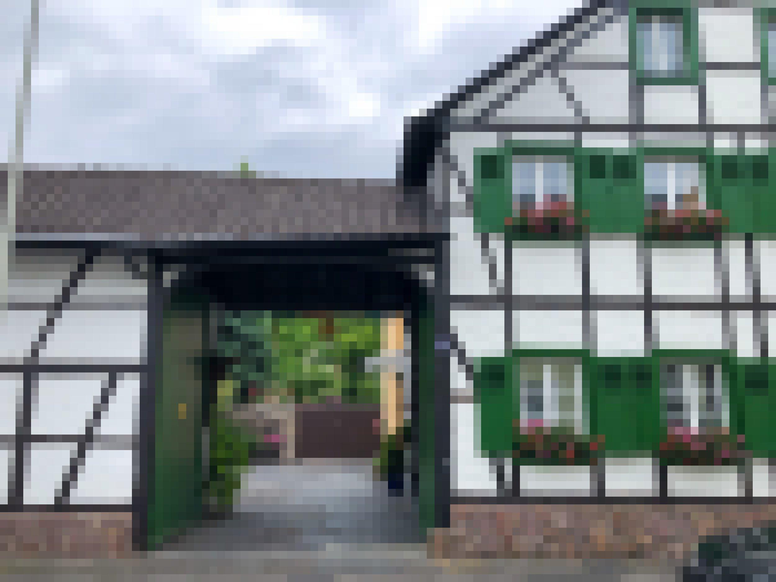 Ein Fachwerkhaus mit grünen Fensterläden und roten und rosafarbenen Geranien vor den Fenstern. Durch die große Einfahrt fällt der Blick auf ein paar Bäume und eine geteerte Fläche.