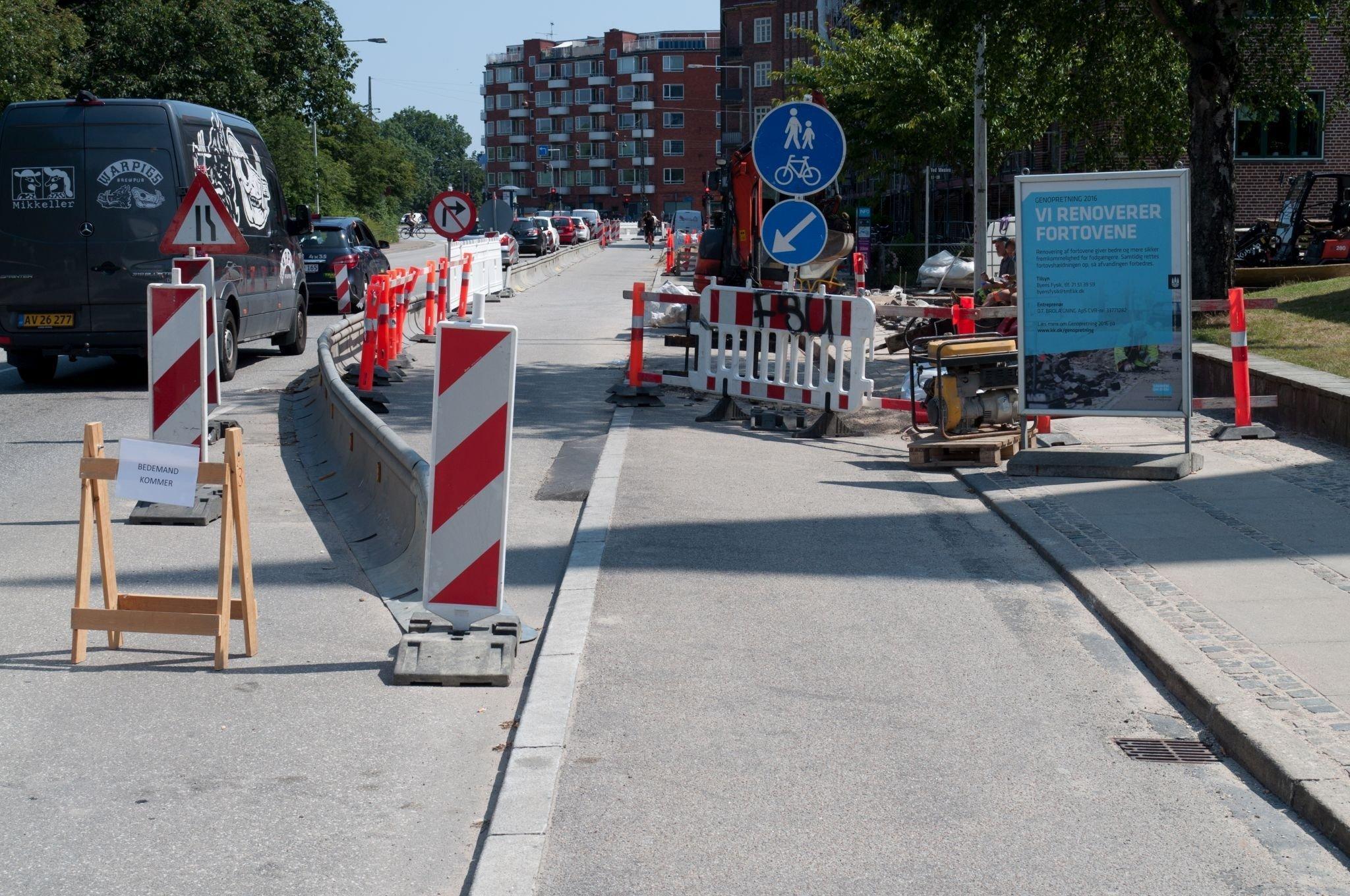 Das Bild zeigt eine Baustelle, bei der Arbeiter einen Radstreifen markiert haben, damit der sichere Radverkehr nicht unterbrochen wird.