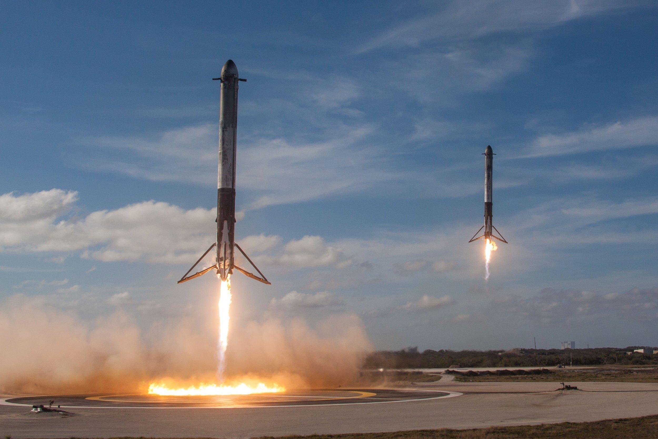 Zwei Booster landen auf einem Asphaltfeld.