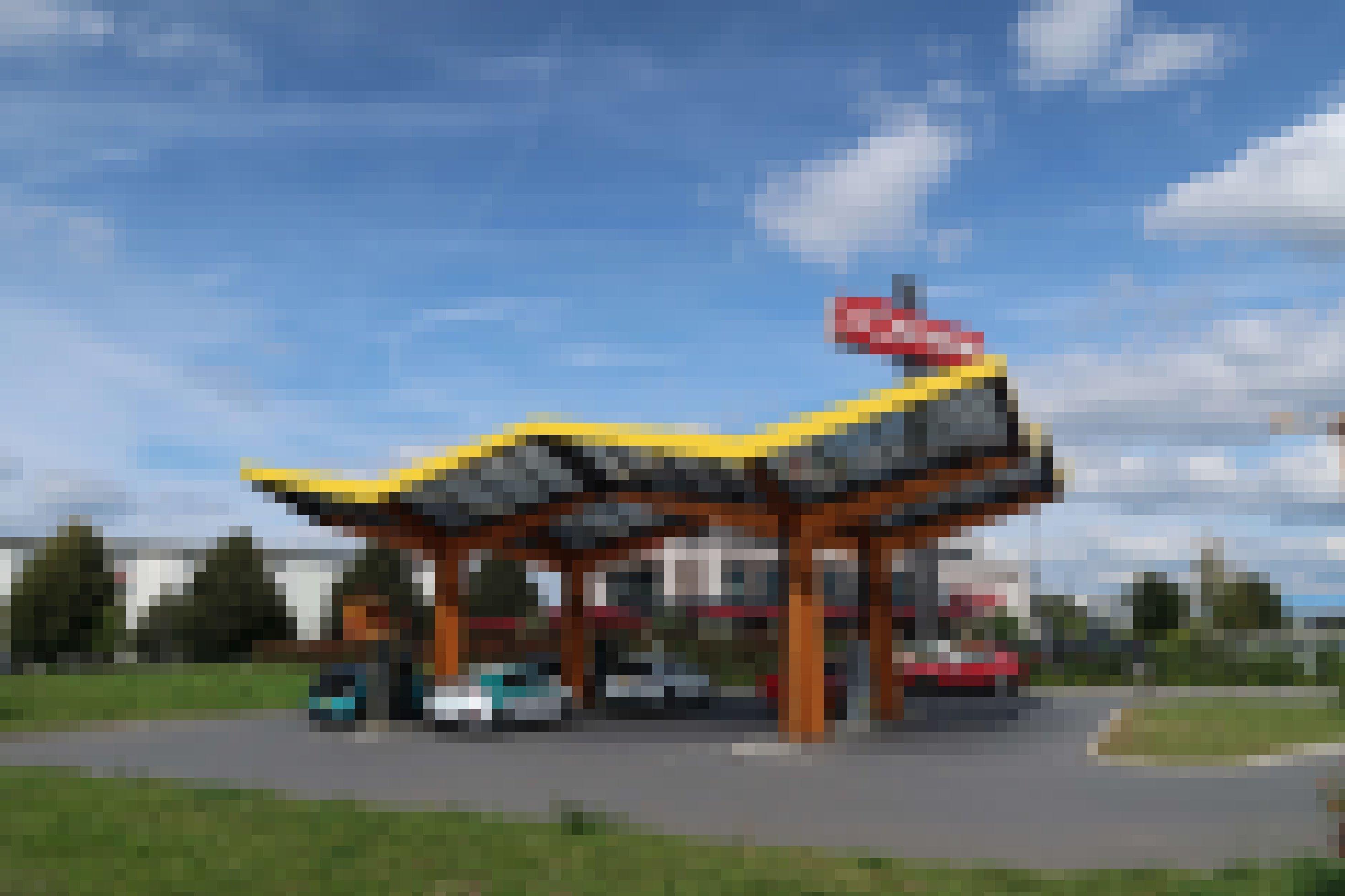 Mehrere Elektroautos laden Strom unter einem Dach, das mit Solarpanels besetzt ist