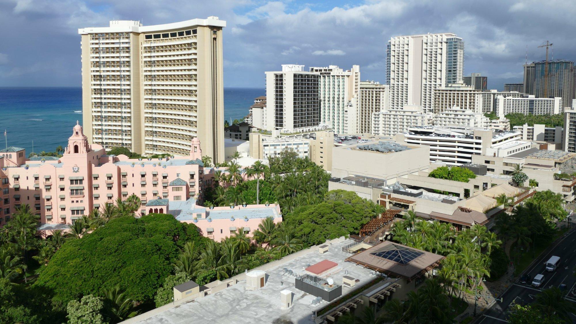 Stadtviertel von Honolulu mit Hochhäusern am Meer, zwischen den Gebäuden stehen Bäume und Palmen.