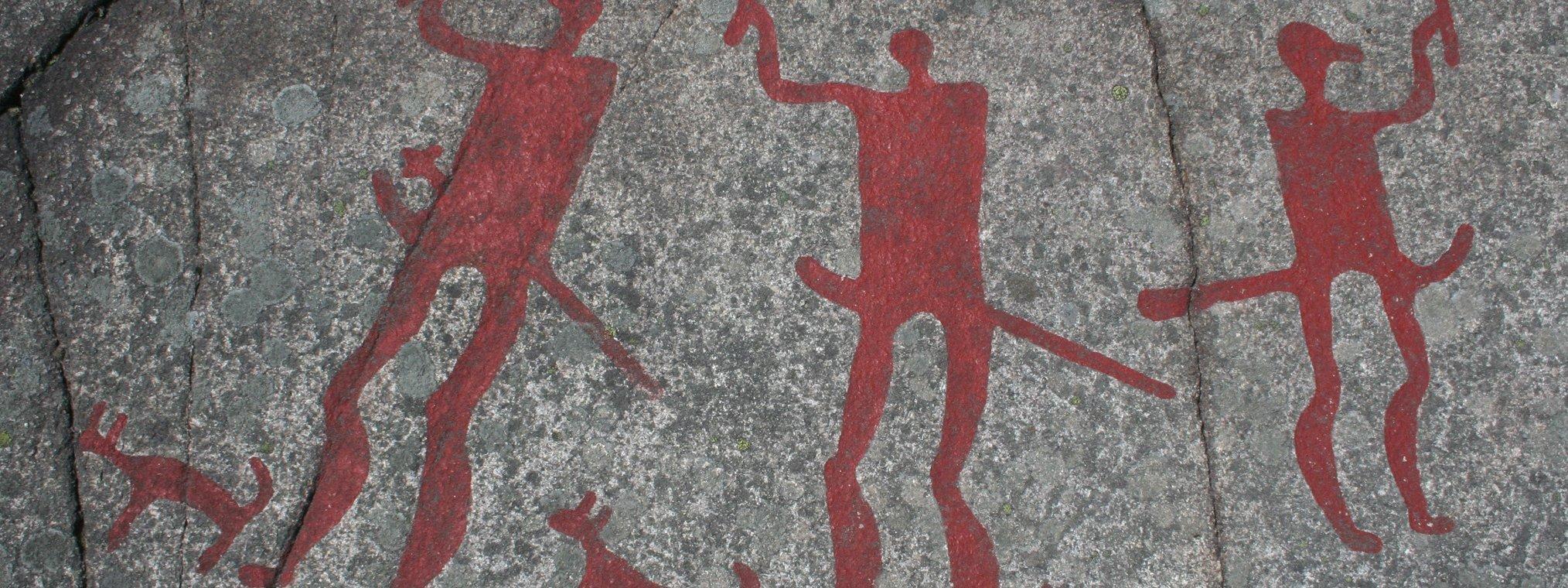 Das Foto zeigt eine Jahrtausende alte Felszeichnung aus der Gemeinde Tanum in Schweden. Prähistorische Menschen haben dort Bilder in den grauen Felsen geritzt und mit leuchtend roten Farben hervorgehoben. Zu sehen sind drei kriegerisch wirkende Figuren sowie drei Hunde.