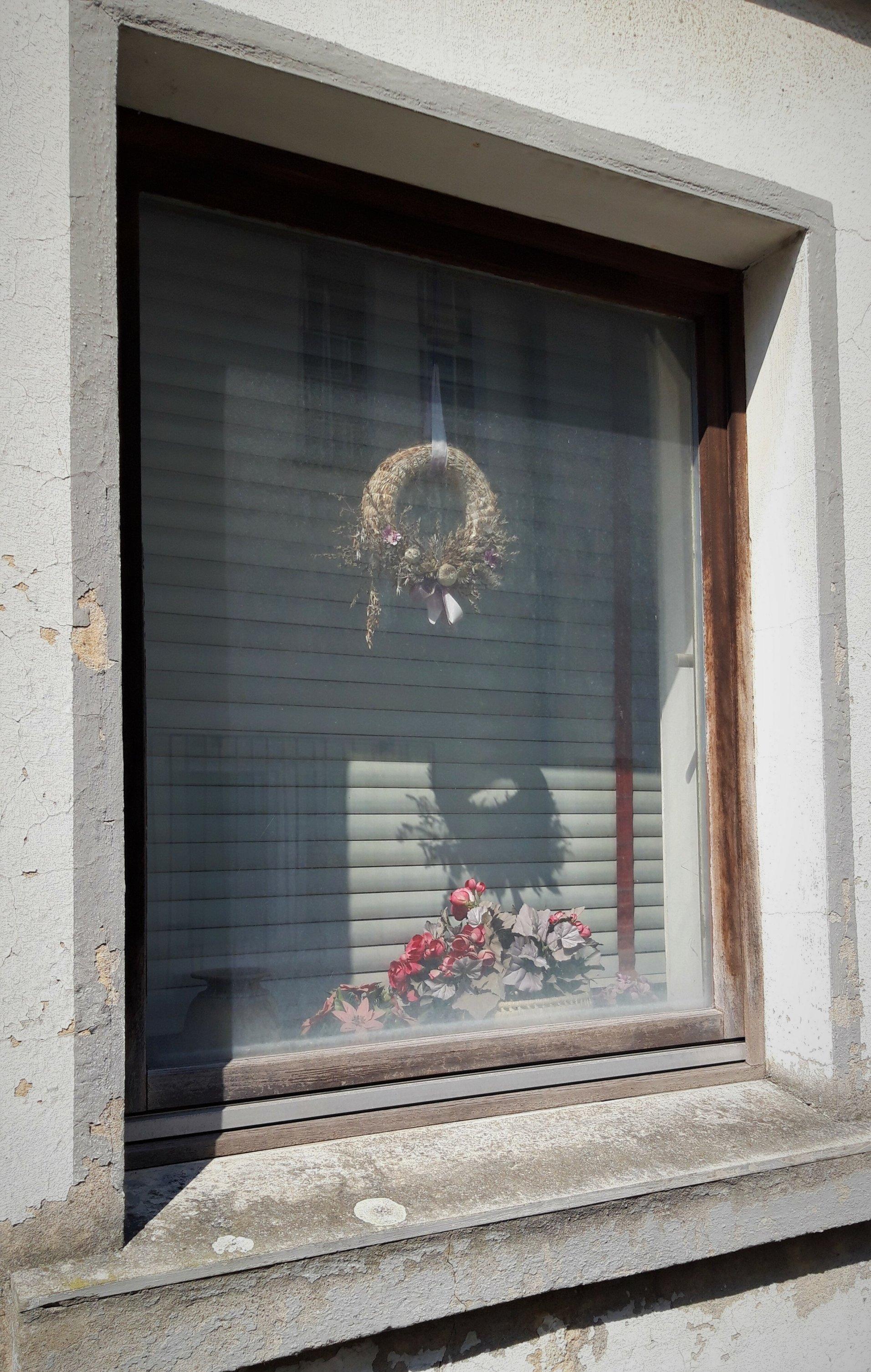 In einer schäbig-weißen Hauswand tut sich eine Fensteröffnung auf. Zwischen Glas und heruntergelassener Jalousie hängt ein staubiger Flechtkranz; darunter steht ein kleines Bouquet aus Plastikblumen.