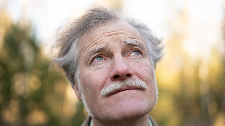 Fieldwriter Gerhard Richter blickt neugierig nach oben in die Bäume