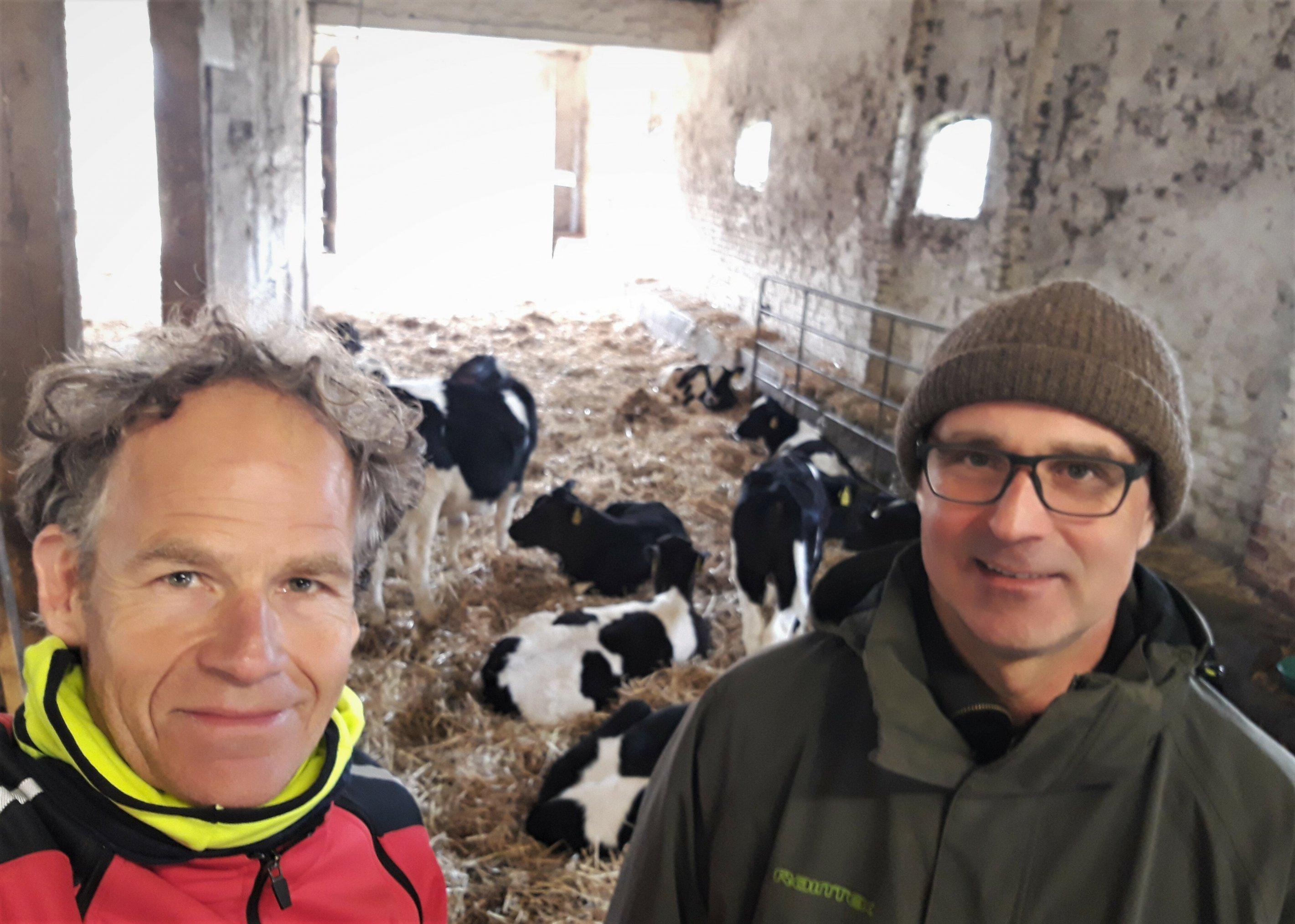 Der Landwirt und der RadelndeReporter äugen in die Kamera. Die meisten Kälber im Hintergrund ruhen auf der Strohunterlage.