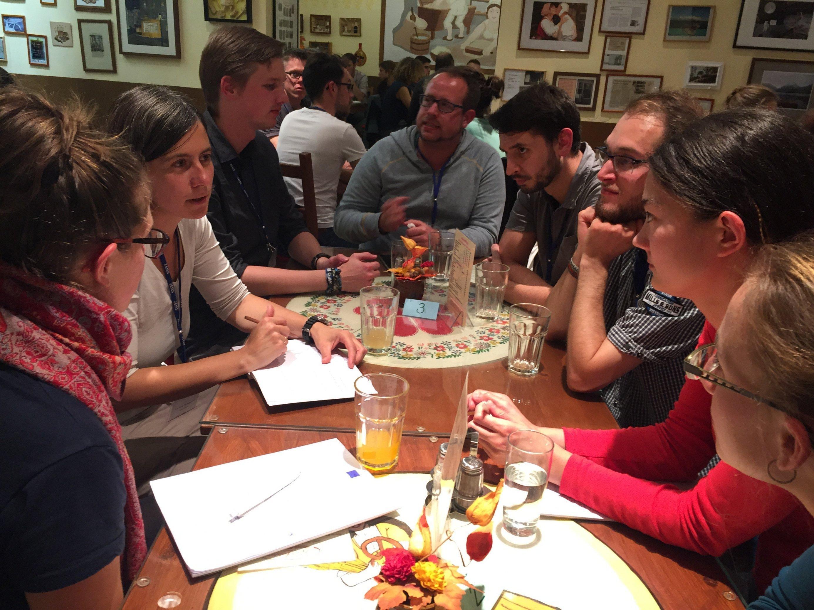 Viele jüngere Menschen sitzen an einem Tisch und hören gespannt Franziska Tanneberger zu.