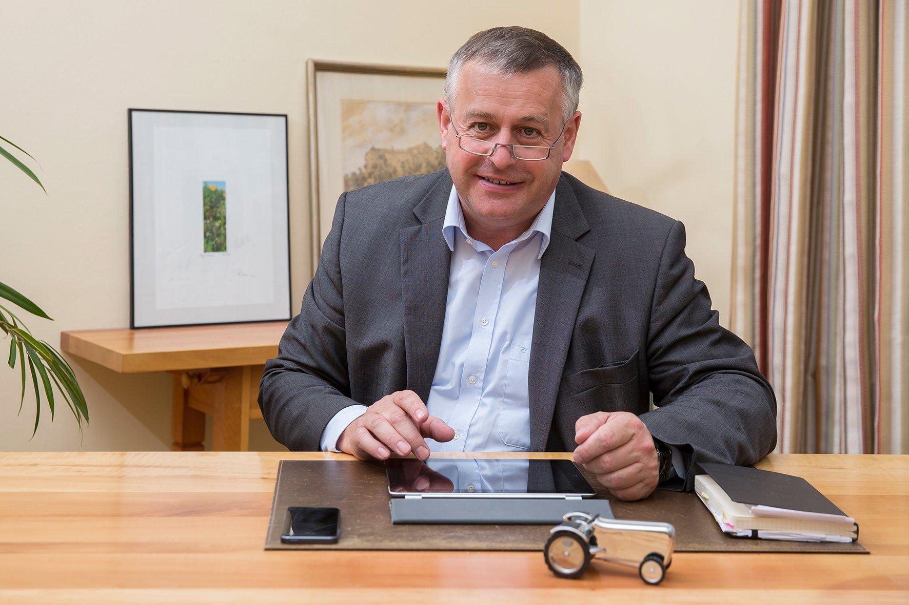Foto von Walter Heidl an seinem Schreibtisch. Vor ihm liegt ein Tablet, ein Smartphone und ein Buch.