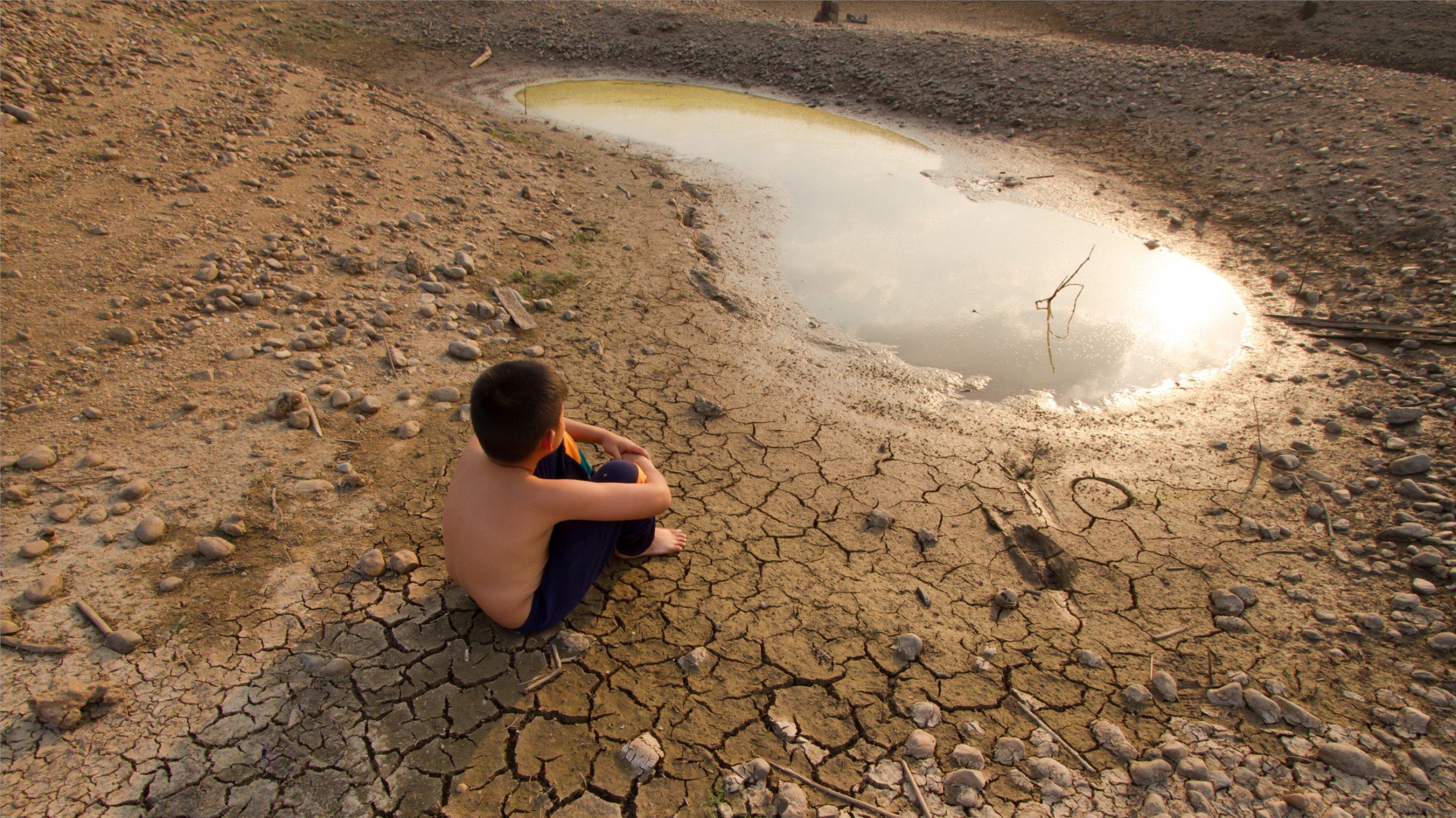 Ein Junge sitzt auf trockenem Boden vor einer Pfütze.
