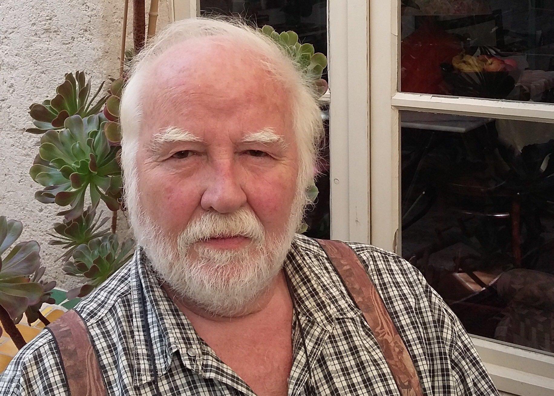 Der Germanist, Romanist, Sinologe und Übersetzer Peter Krauss sitzt vor einem Haus.