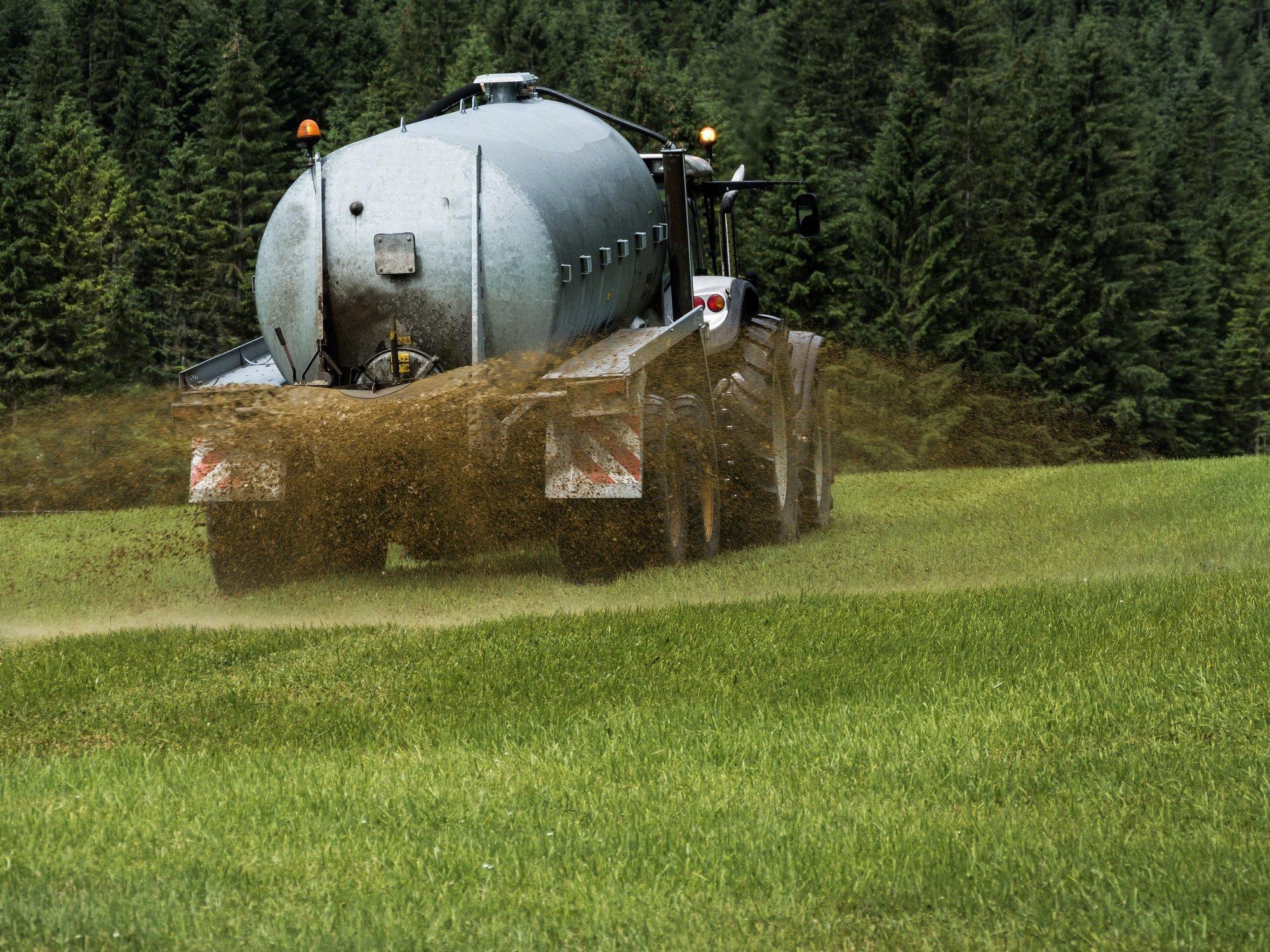 Ein Trecker der gerade Gülle über einem Feld versprüht.