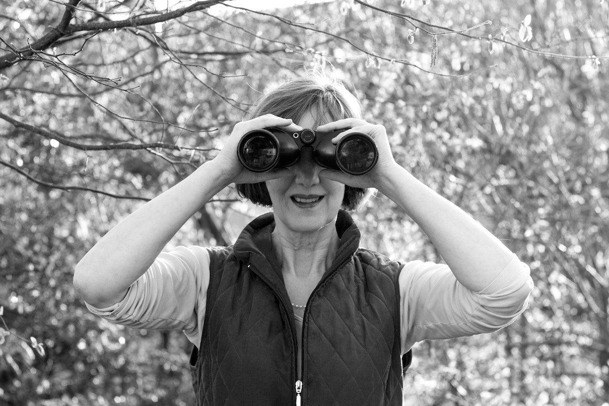 Johanna Romberg schaut durch ein Fernglas zur Kamera.