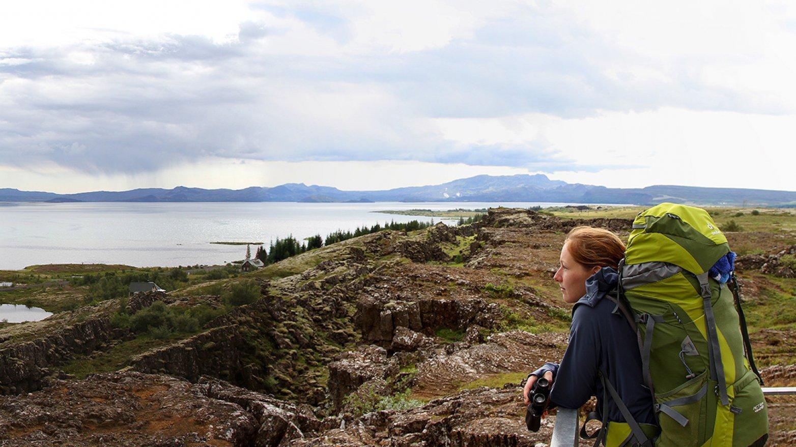 Lisa Pannek im Þingvellir-Nationalpark in Südwestisland. Sie trägt einen großen Wanderrucksack und steht mit einem Fernglas in der Hand vor einer felsigen Landschaft. Im Hintergrund sieht man Wasser und Berge.