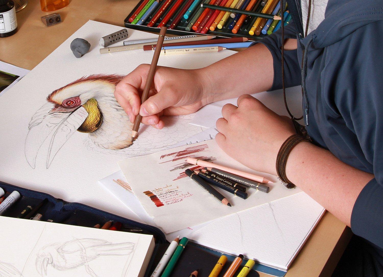 Der Schreibtisch von Lisa Pannek. Buntstifte, Radiergummis, Zeichenpapier und ein Skizzenbuch. Eine Frau malt an einem Bild.