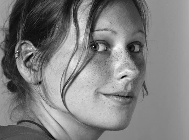 Die Illustratorin Lisa Pannek. Eine Frau mit Sommersprossen in schwarz/weiß.