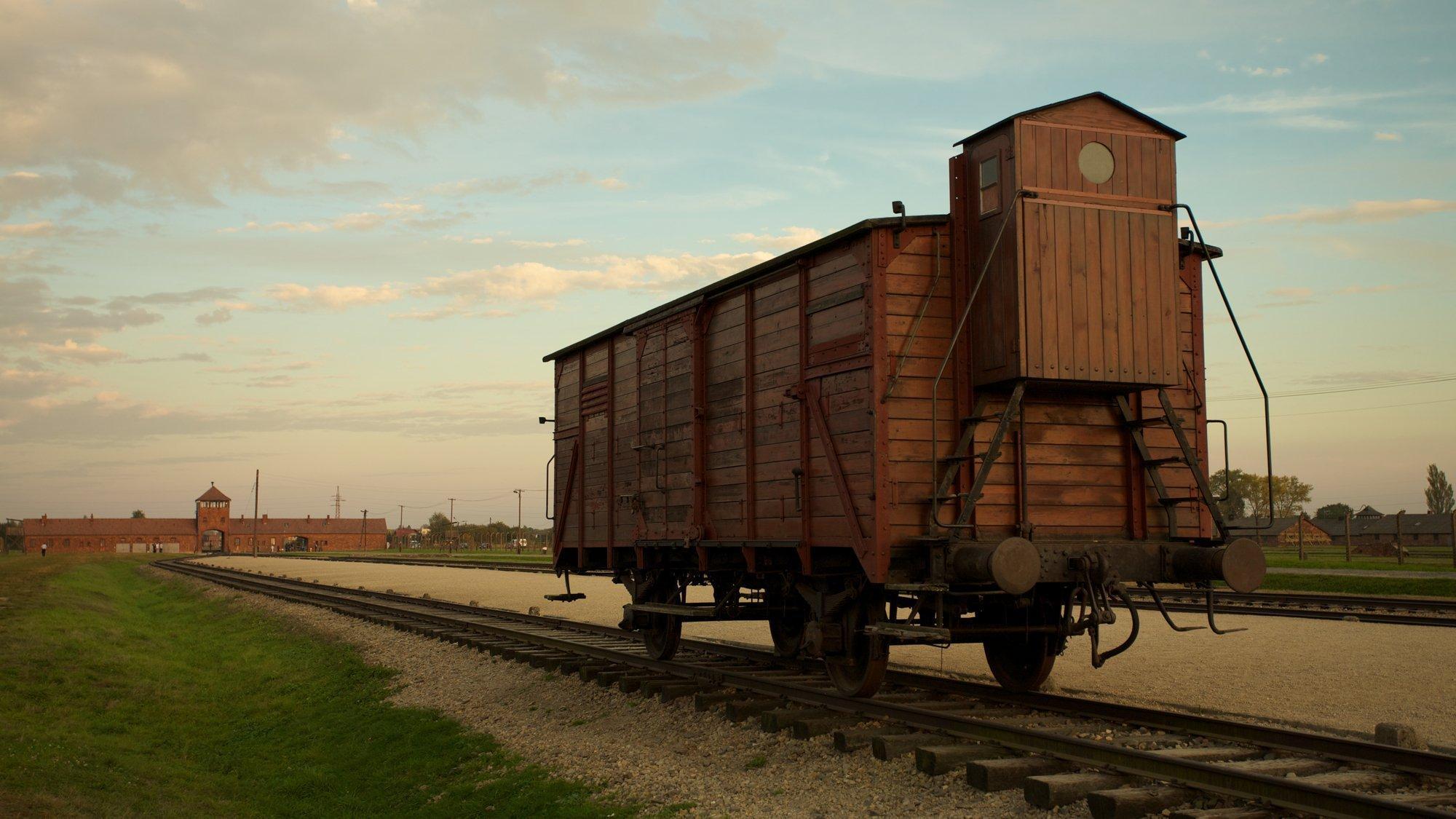 Ein einzelner, geschlossener Waggon auf Schienen. Im Hintergrund sind man das Konzentrationslager Auschwitz-Birkenau
