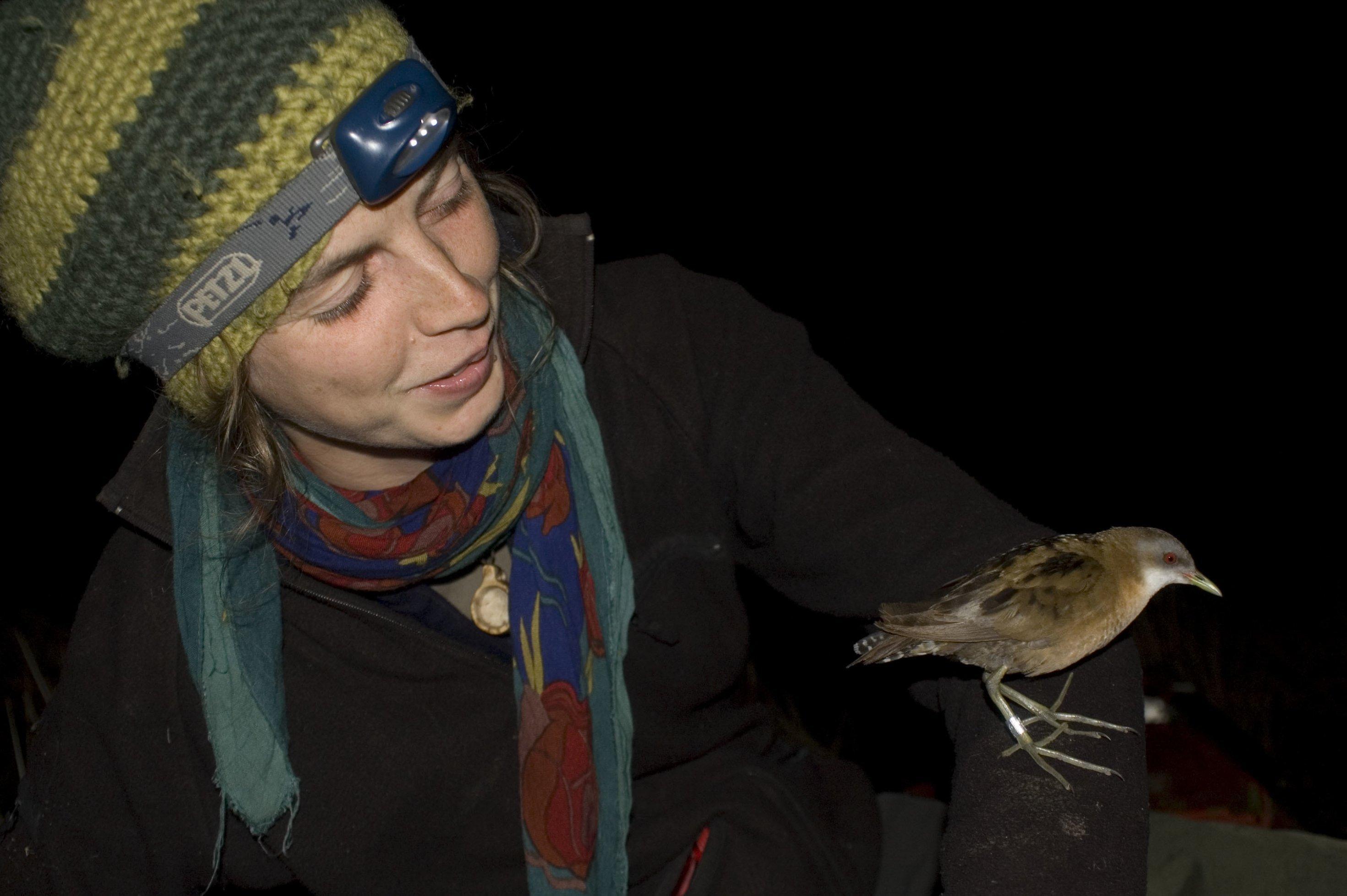 Nina Seifert hat ein kleines Sumpfhuhn auf dem Arm sitzen. Es ist nachts.
