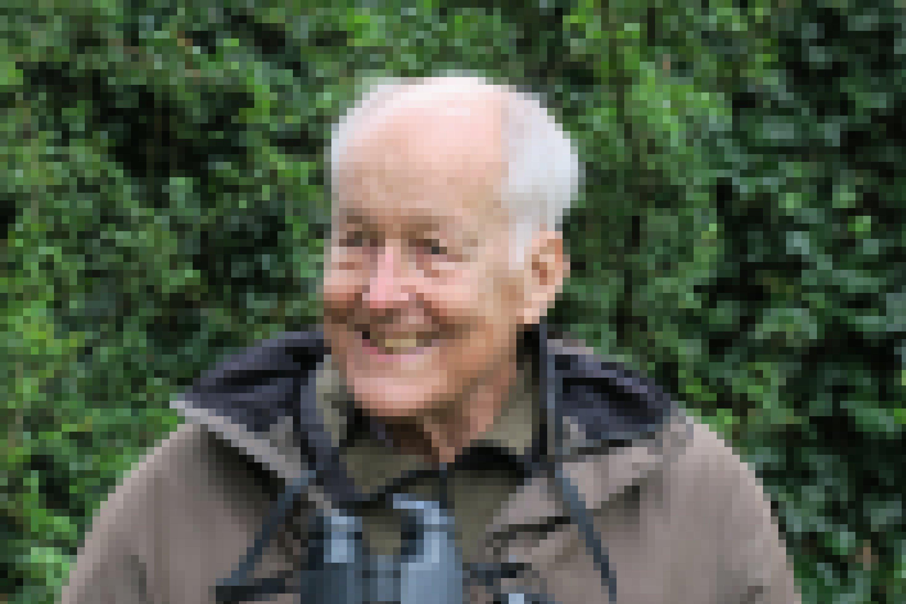 Portrait-Aufnahme von Carl-Albrecht von Treuenfels. Er steht lächelnd mit einem Fernglas um den Hals vor Büschen.
