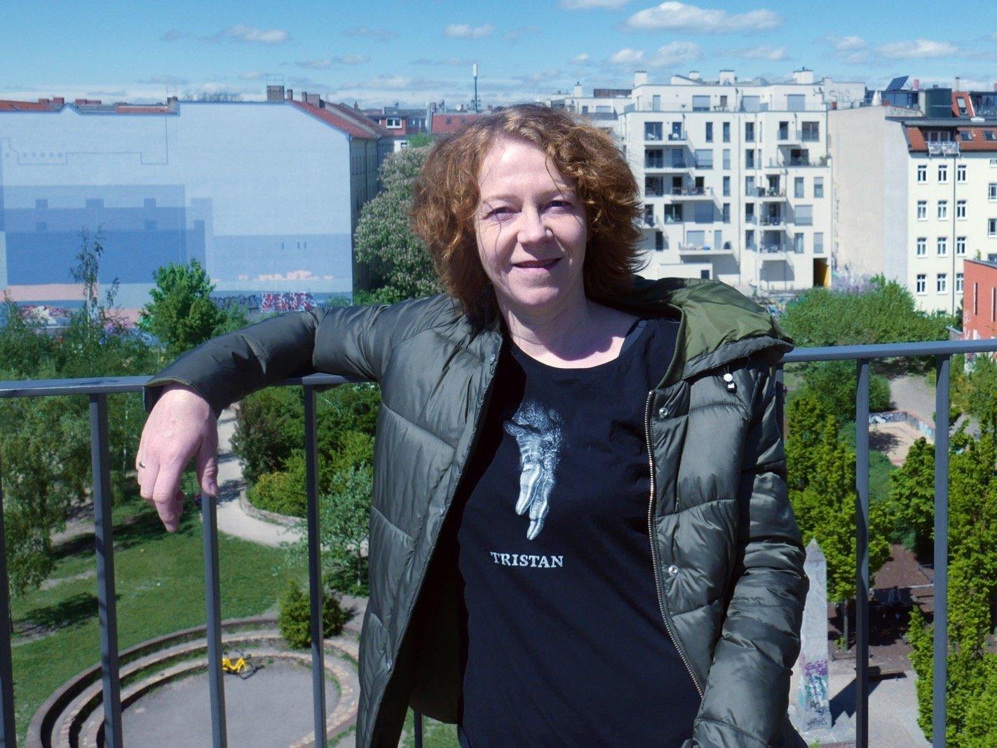 Christiane Habermalz lehnt an einem blauen Geländer. Im Hintergrund erkennt man einen Park und mehrstöckige Wohnhäuser.