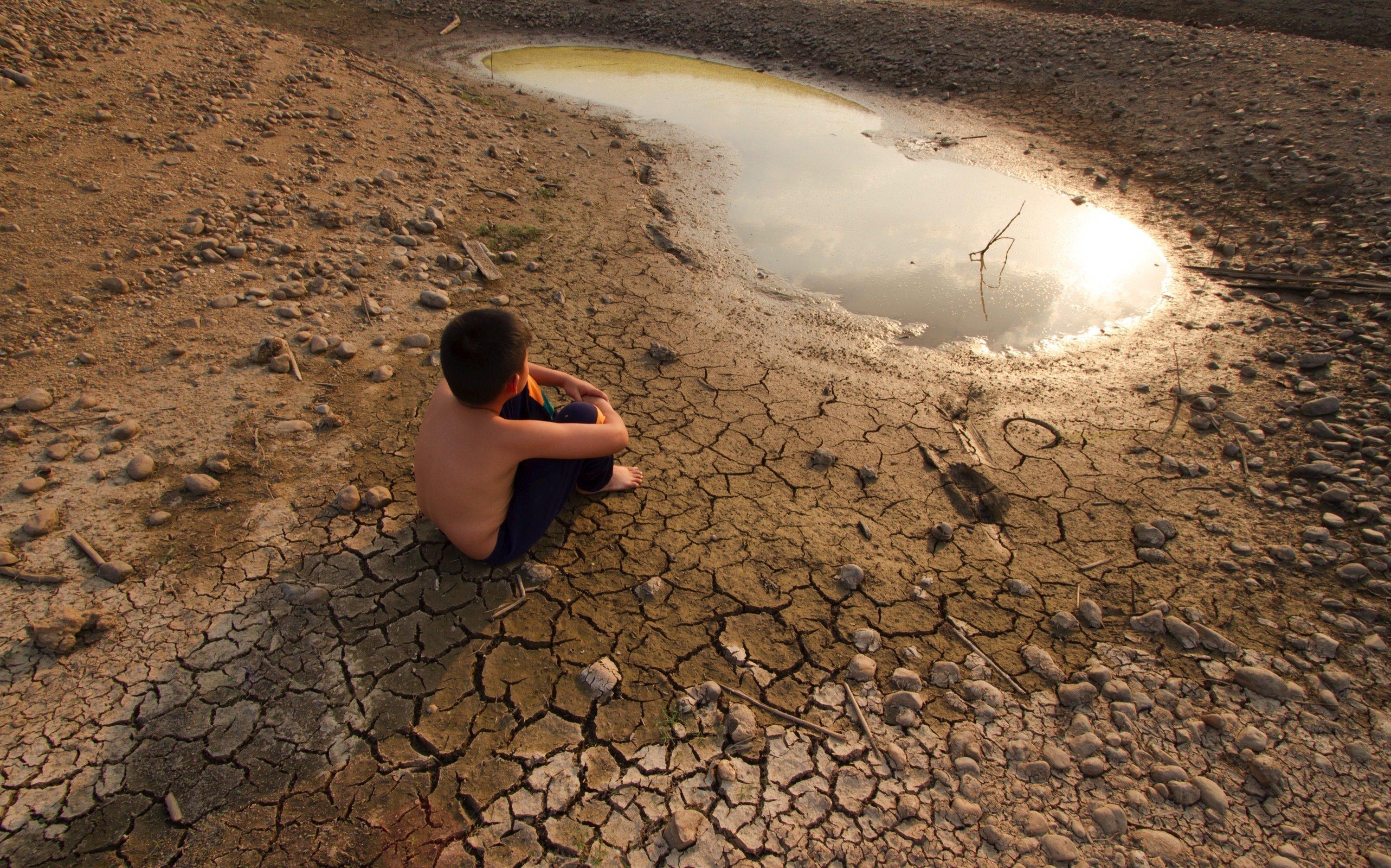 Ein Junge sitzt auf ausgetrocknetem, gerissenem Boden vor einer Pfütze.