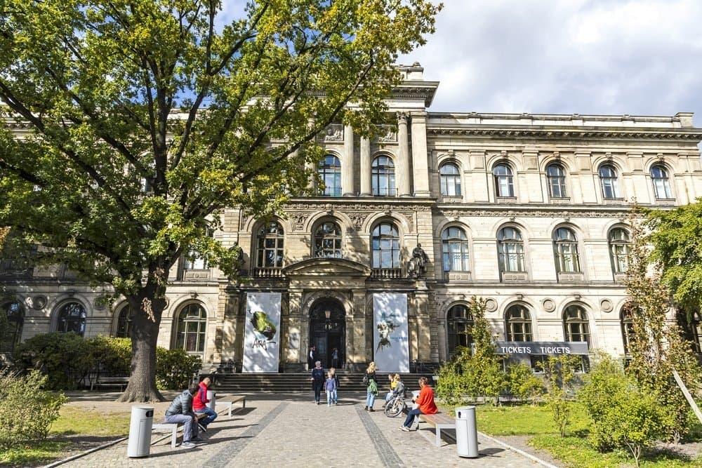 Das Museum für Naturkunde in Berlin. Ein helles, dreistöckiges Gebäude.Vor dem Eingang sind ein paar Bänke auf denen Menschen sitzen.