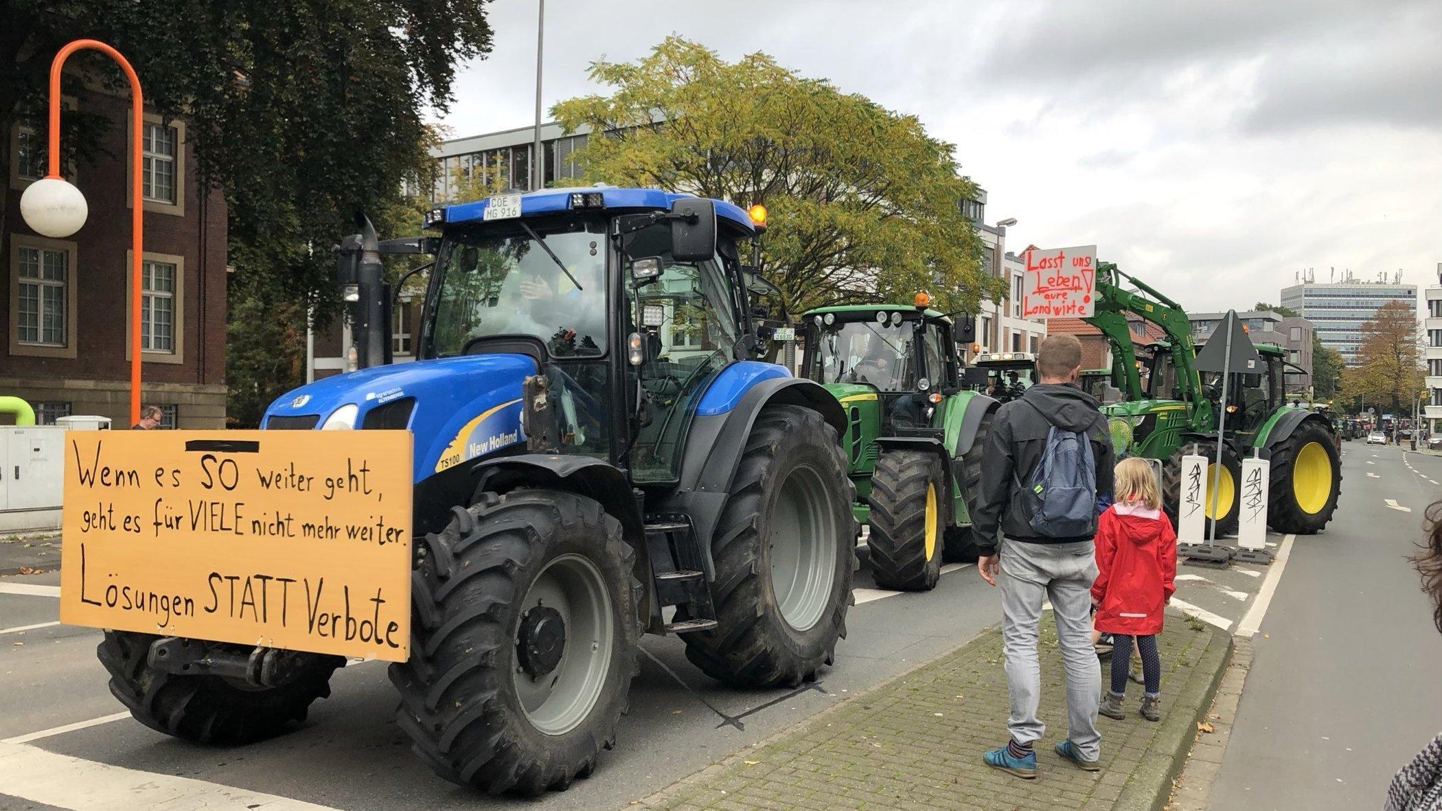 Trecker fahren auf einem Bauernprotest in Münster. 23.10.2019. Ein Mann schaut sich mit seinem Kind das Geschehen vom Straßenrand aus an.