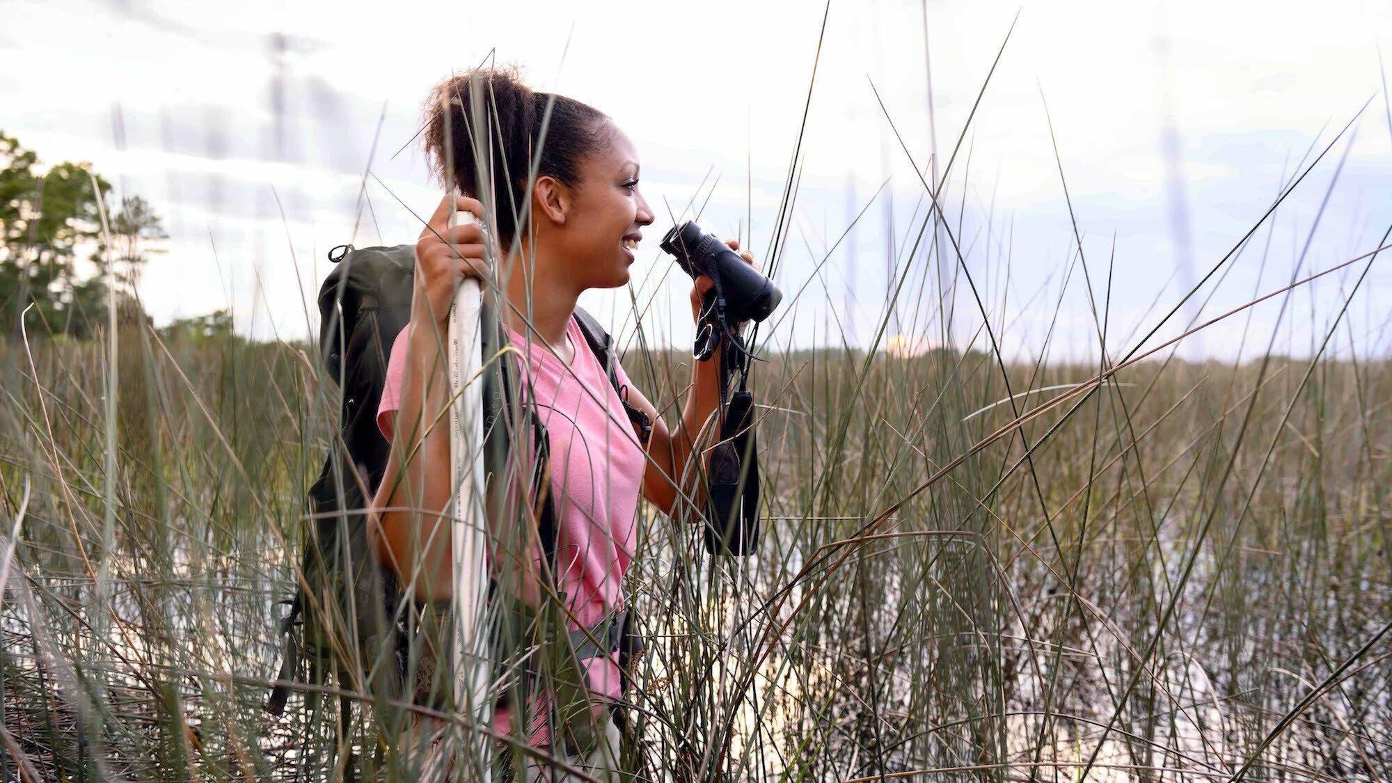 Zu sehen ist die junge Ornithologin Corina Newsome, die mit einem Fernglas in der Hand in einem Sumpf bis zur Hüfte im Wasser steht.