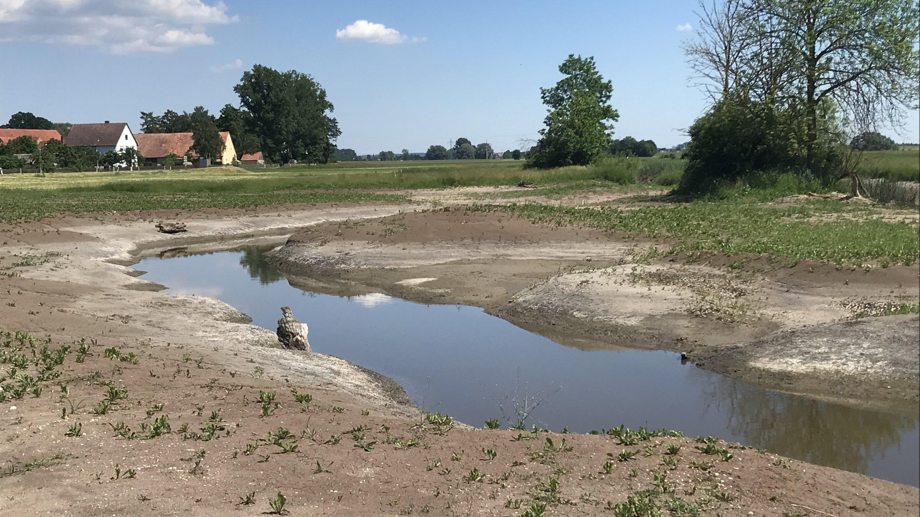 Der schmale Fluss mit abgeflachtem Ufer.