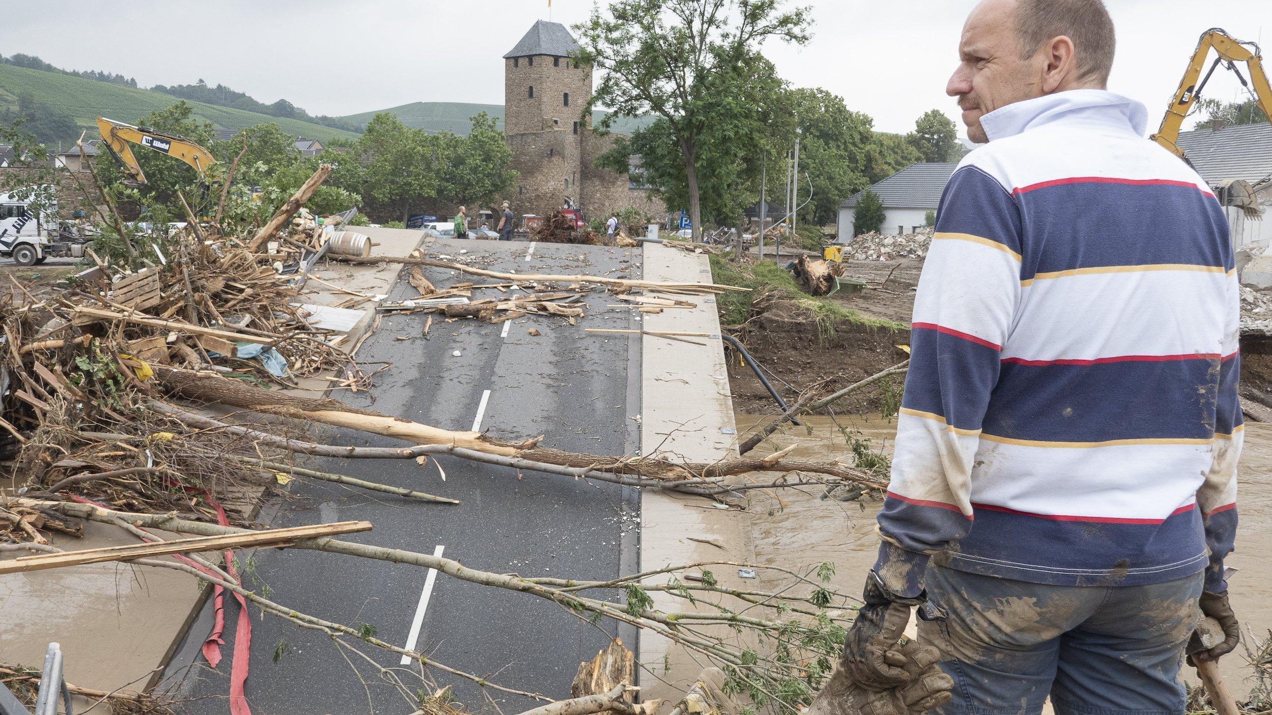Vorn rechts steht ein Mann im geringelten Sweatshirt vor der Brücke, deren Fahrbahn abgesackt ist und auf der Bäume liegen. Der Mann schaut nach links in das verwüstete Flusstal der Ahr.