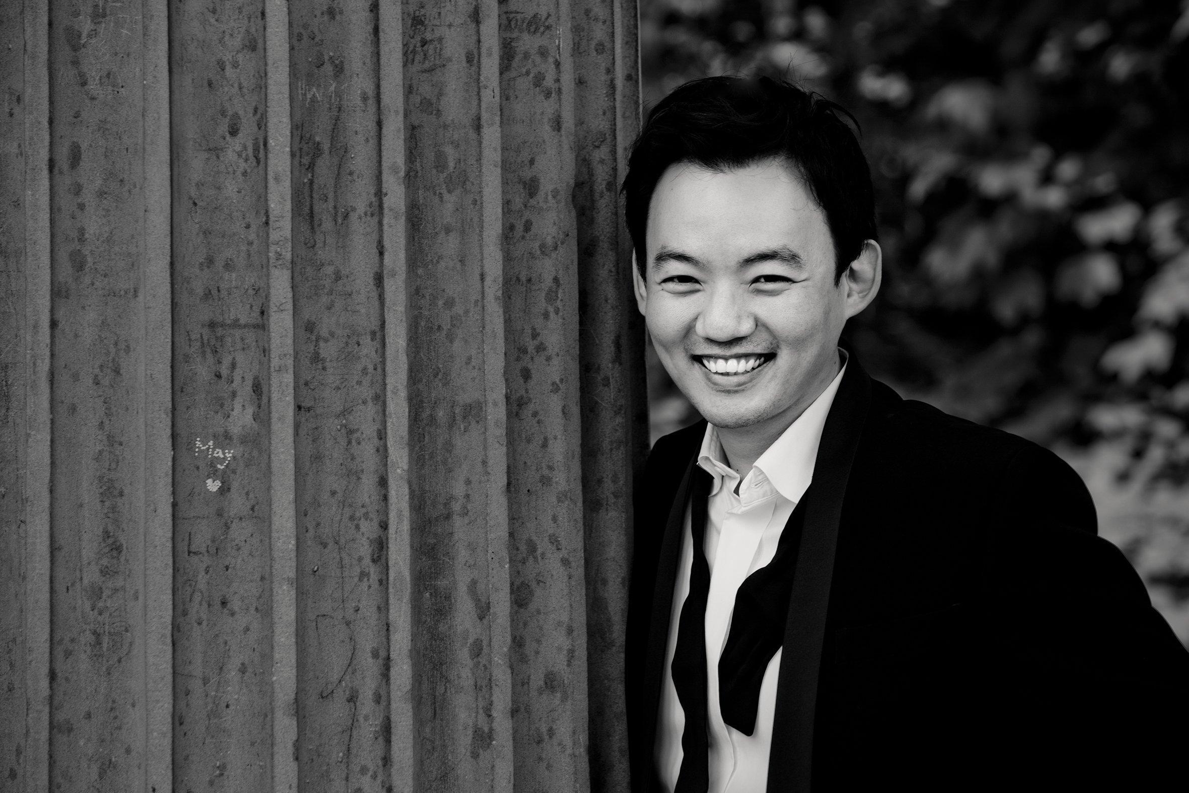 Der Pianist William Youn steht lachend, draußen vor einer Wand