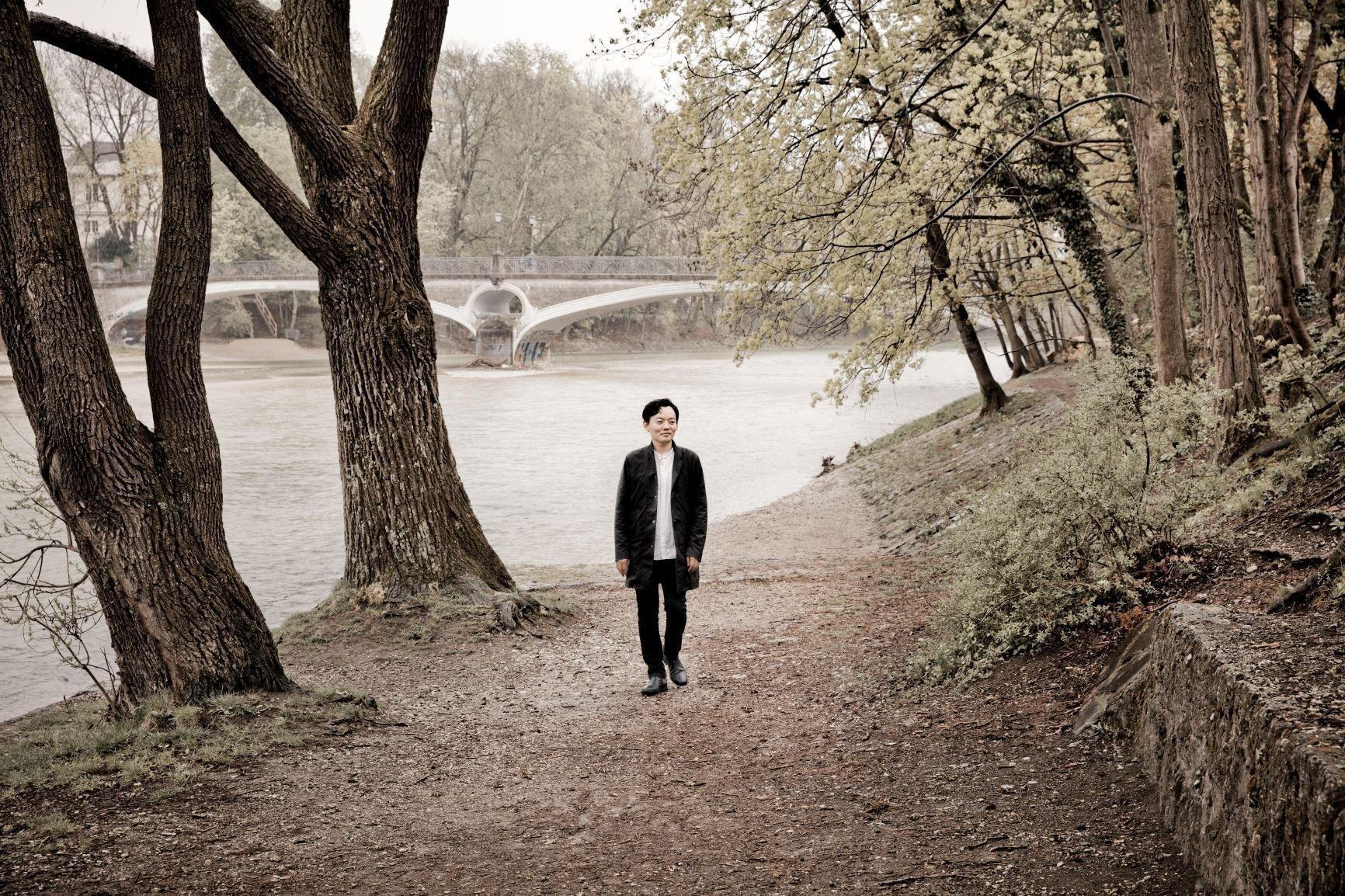 Der Pianist William Youn läuft im weißen Hemd und schwarzer Jacke am Ufer eines Flusses entlang.