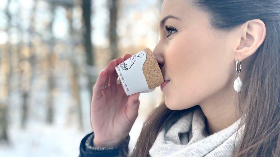 Eine Frau trinkt aus einem kleinen essbaren Kaffeebecher.