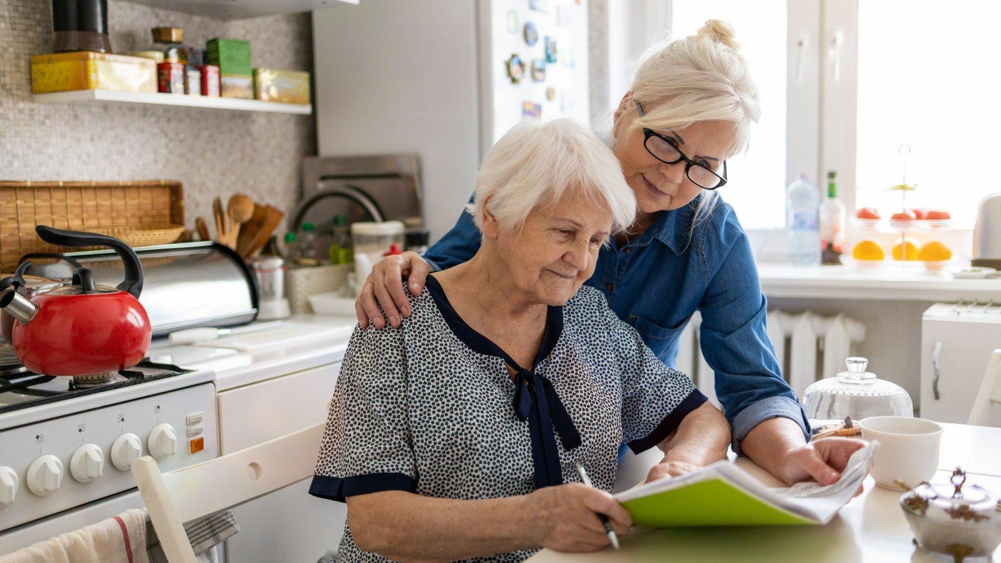 Eine Frau hilft ihrer alten Mutter am Küchentisch mit Papierkram.