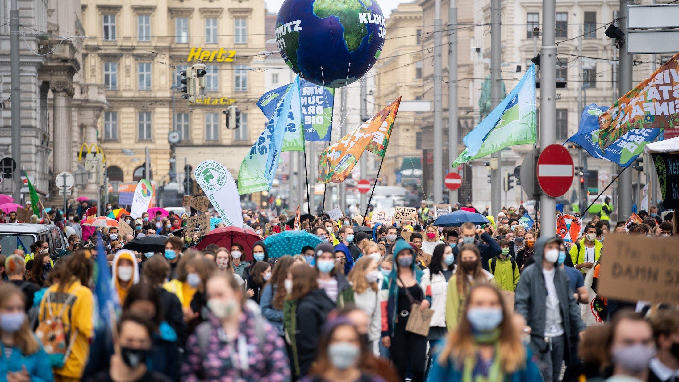 Dargestellt ist eine große Menschenmenge, die sich mit Bannern und Plakaten durch die Innenstadt von Wien bewegt. Auch eine aufblasbare Erdkugel haben die Demonstranten von Fridays for Future dabei. Im Gegensatz zu den Querdenkern tragen sie Gesichtsmasken.