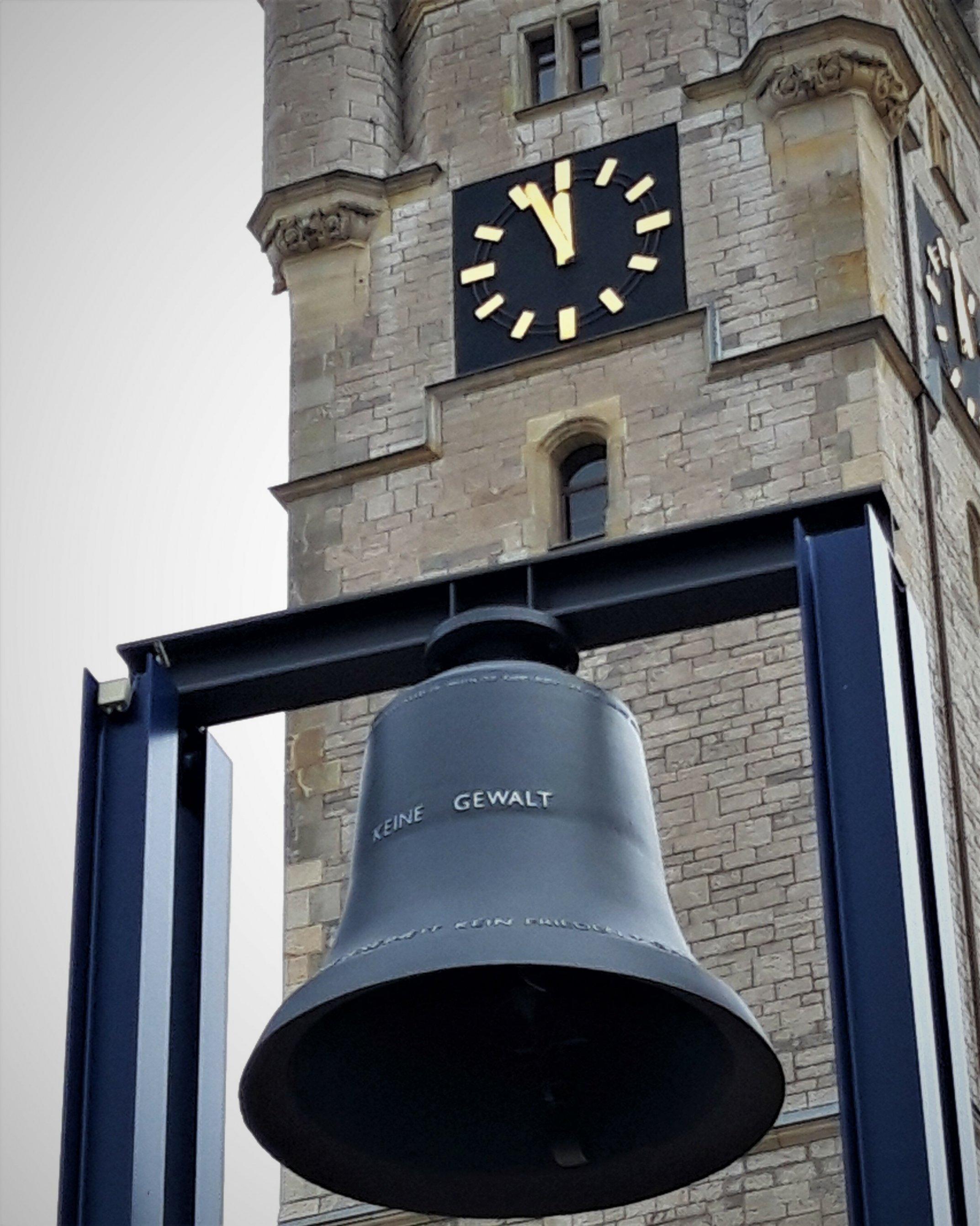 """Auf der Glocke vor dem Rathausturm steht """"keine Gewalt"""". Die Tumuhr zeigt fünf vor Zwölf."""