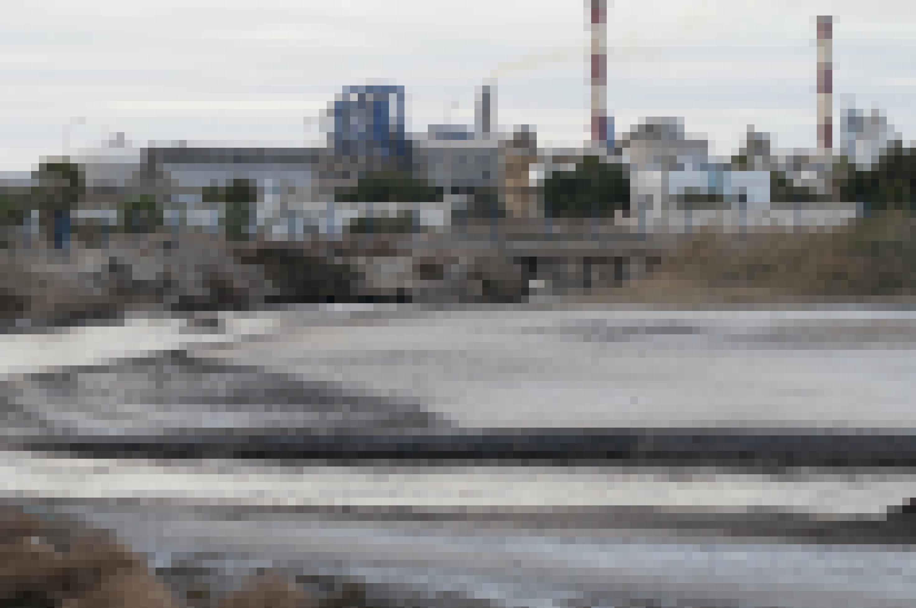 Eine schwarze, zähflüssige Masse wird aus einer Fabrik geleitet.