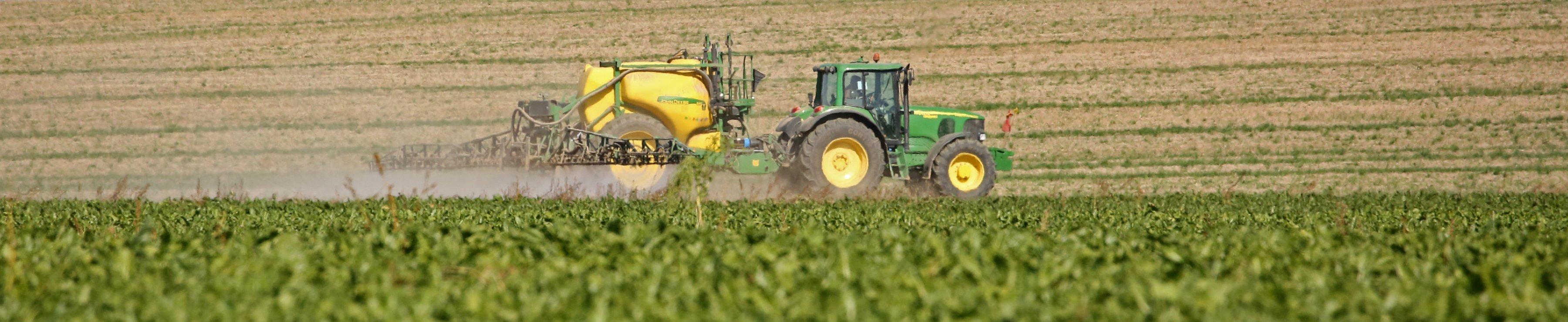 Ein Landwirt versprüht mit seinem Traktor Pestizide auf einem Acker.