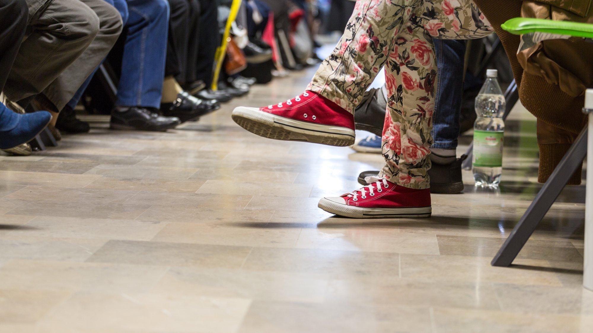 Bild mit vielen Beinen von Menschen, die in einem Wartezimmer sitzen.