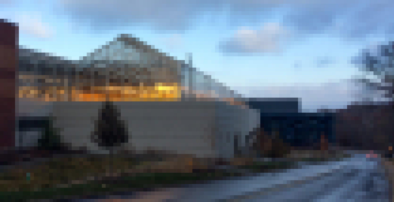 Auf einem fensterlosen hellbeigen Gebäude steht ein Gewächshaus mit Spitzdach. Im Innern leuchtet gelbes Licht.