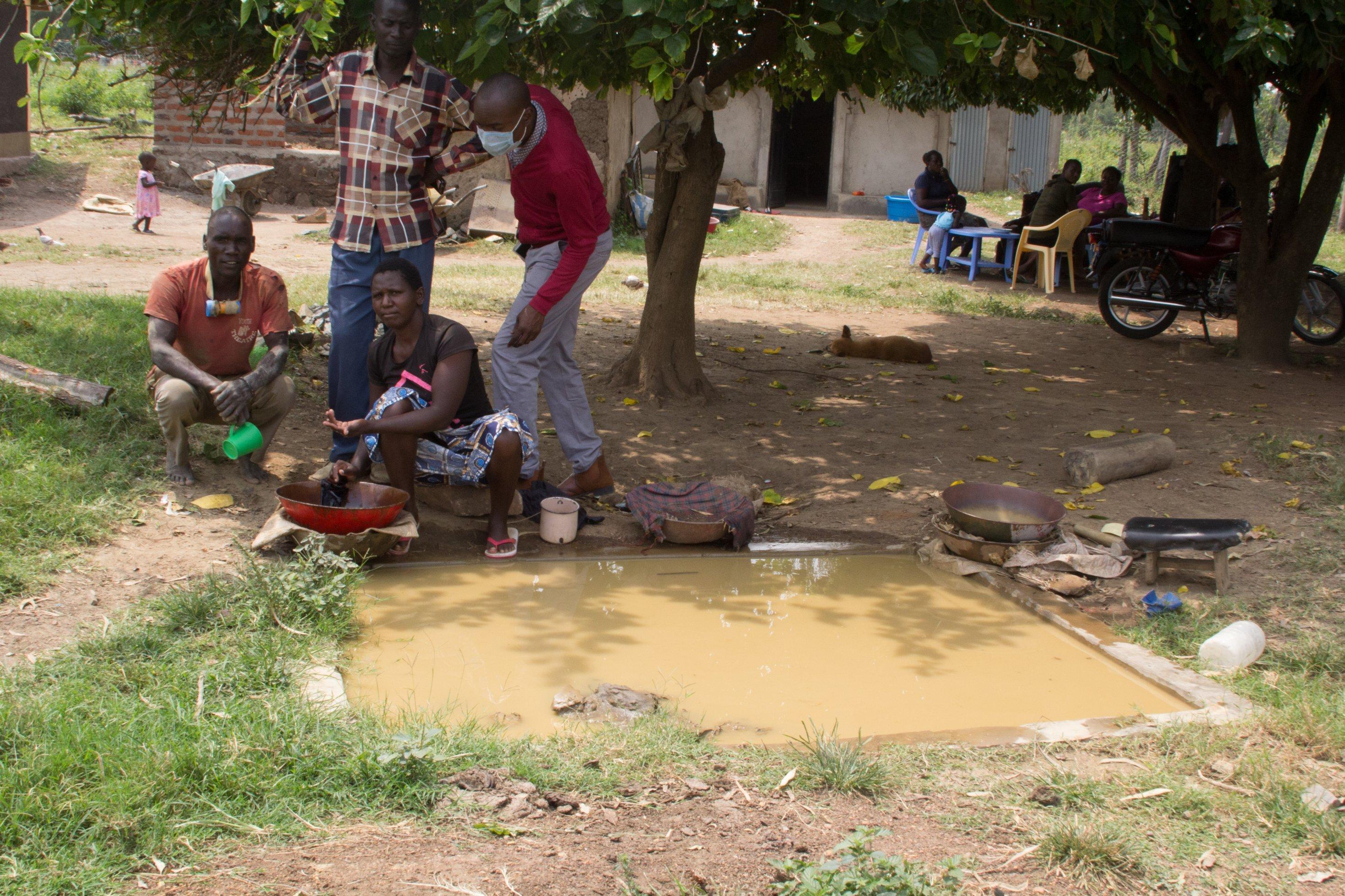 Einige Goldwäscherinnen und Goldwäscher hocken vor einer Wasserstelle. Den Staub aus dem Erdreich waschen sie mit quecksilberhaltigem Wasser.