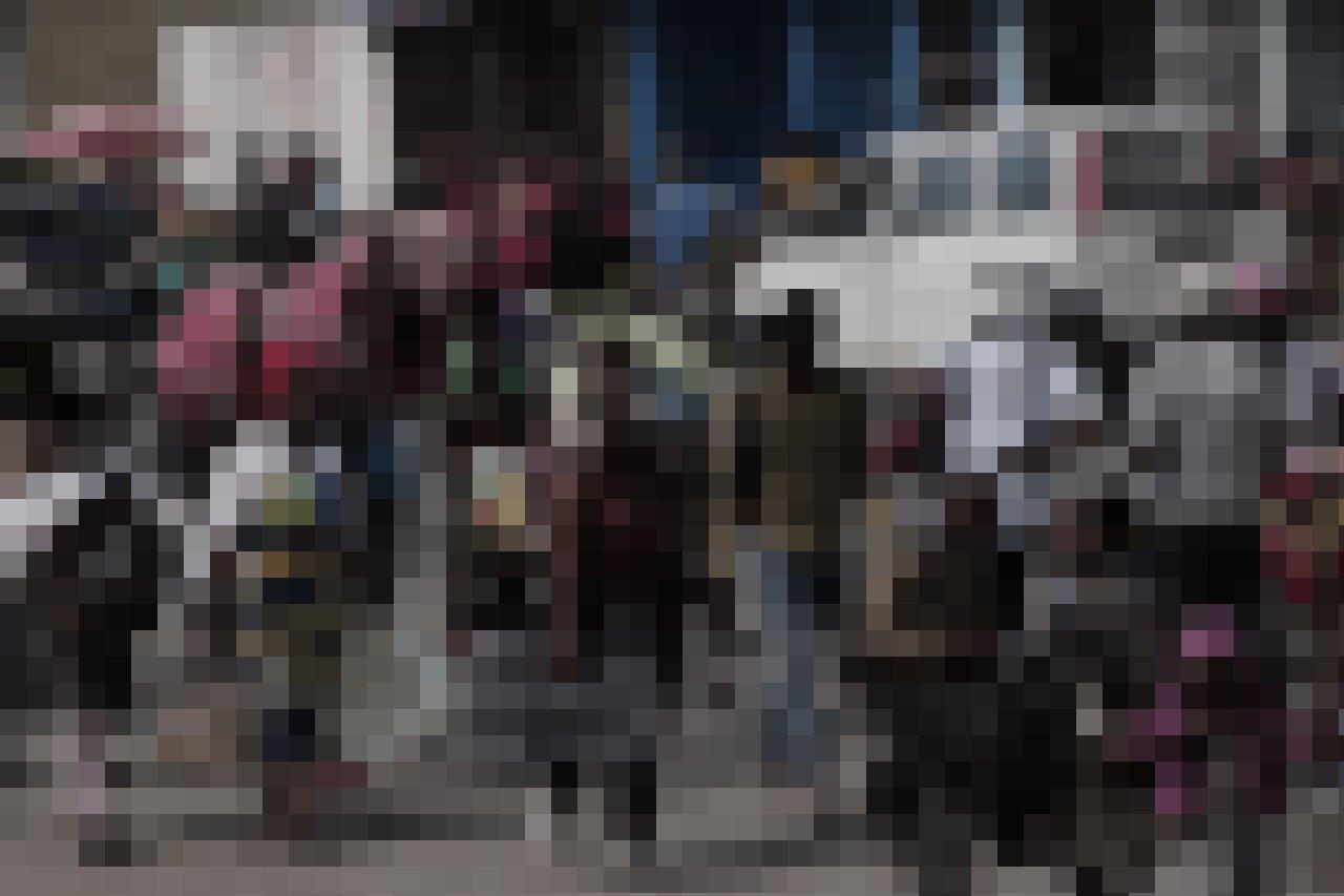 Man sieht viele Menschen auf der Straße, die Habseligkeiten wie Matratzen tragen, manche auch ihre Kleinkinder.