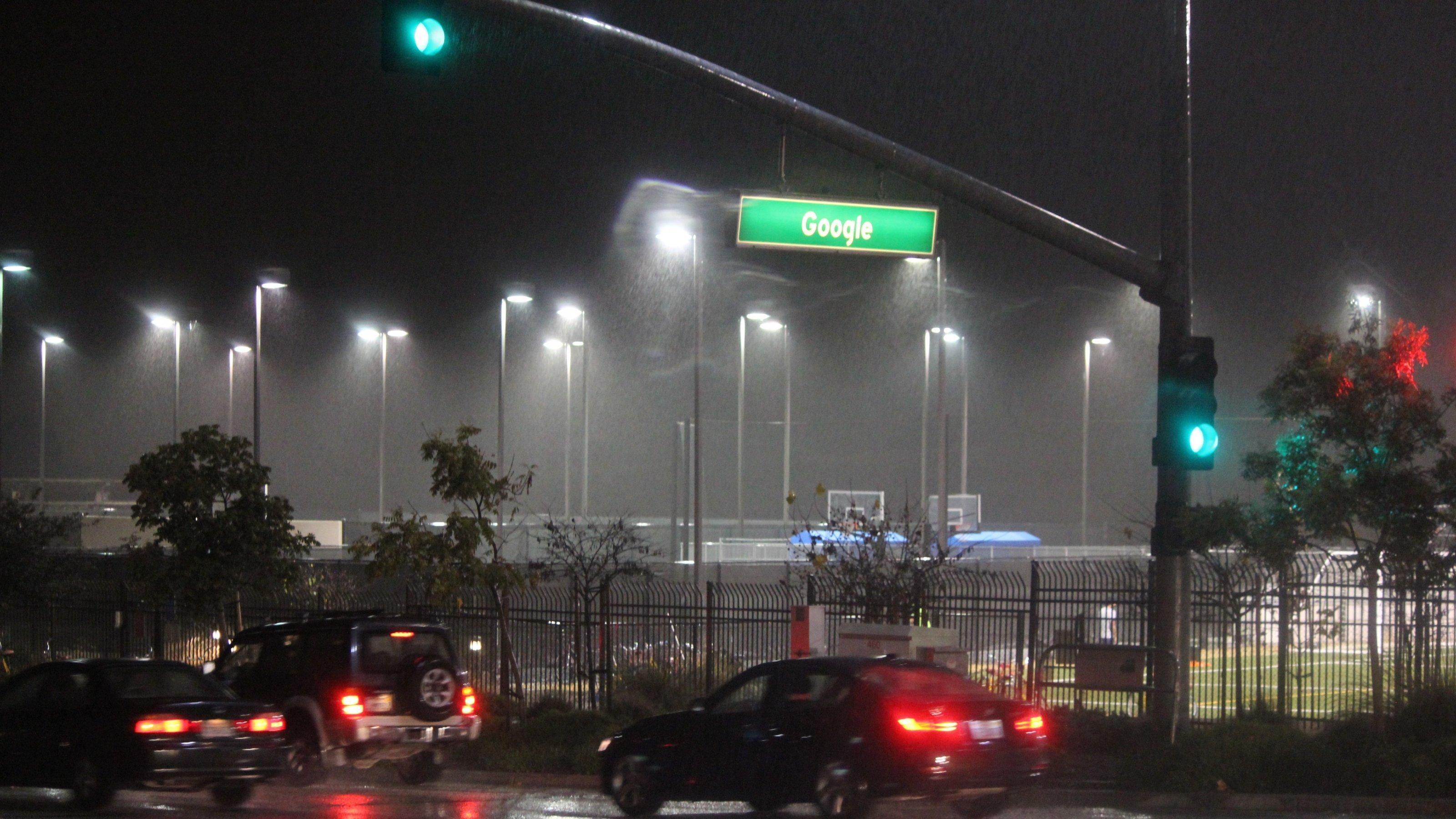 Autos fahren bei Nacht über eine Straße. Auf einem Straßenschild steht Google.