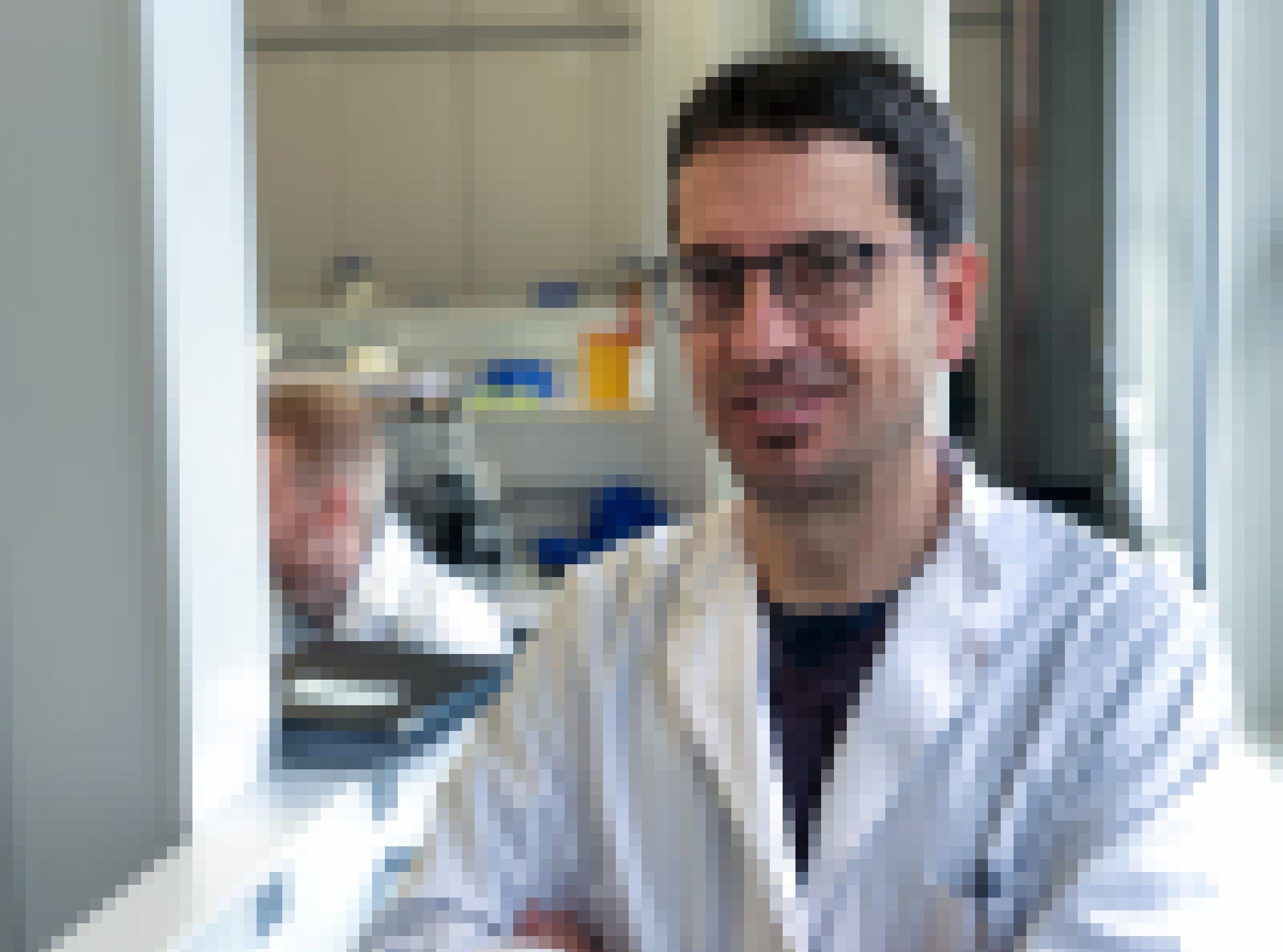 Ein dunkelhaariger Mann mit weißem Kittel und schwarzer Brille steht in einem Labor und schaut in die Kamera.