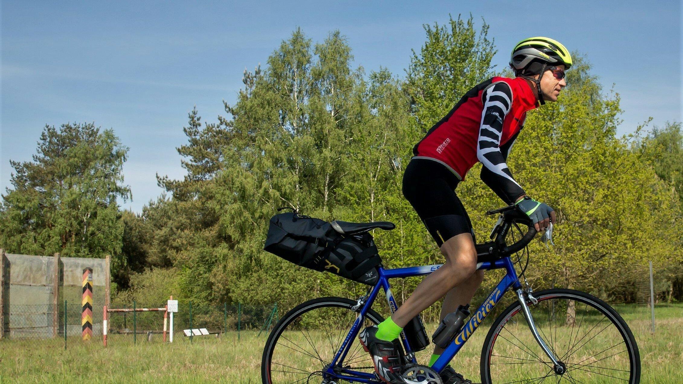 Martin C Roos in Radkluft auf seinem Rennrad, im Hintergrund ein ehemaliger DDR-Grenzpfahl und Teile eines Metallstreckzauns.