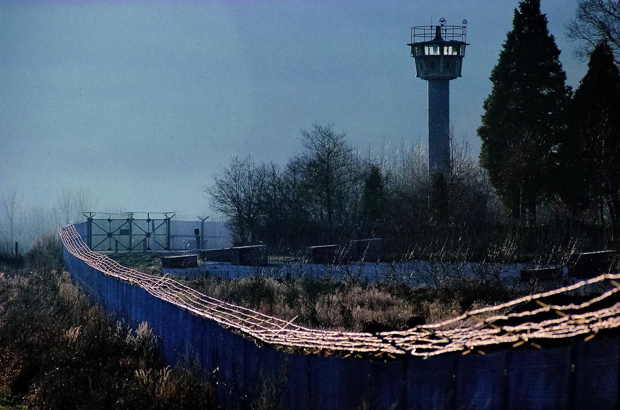 Stacheldrahtbewehrte Zäune ziehen sich vor einem DDR-Wachturm entlang. Die Anlage wirkt brutal.