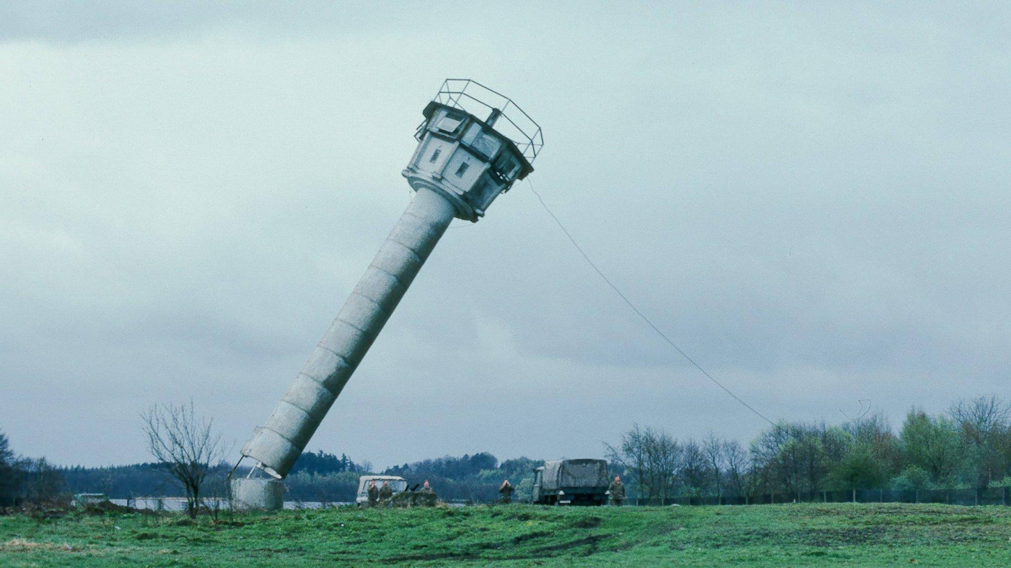 Ein Bundeswehr-Lastwagen reißt mit einer langen Leine einen Wachturm an der innerdeutschen Grenze um, der Turm ist im Fallen zu sehen.