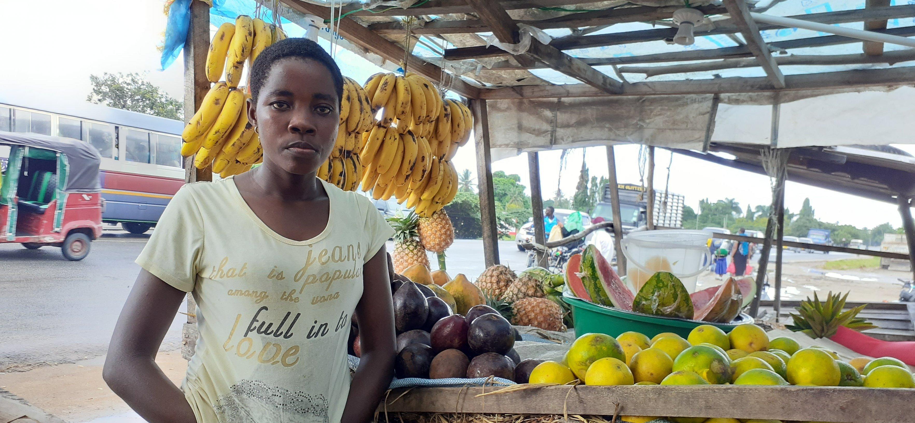 Eine junge Frau steht vor ihrem Marktstand. Bananen, Ananas, Papaya und Avocados sind sorgfältig angeordnet.