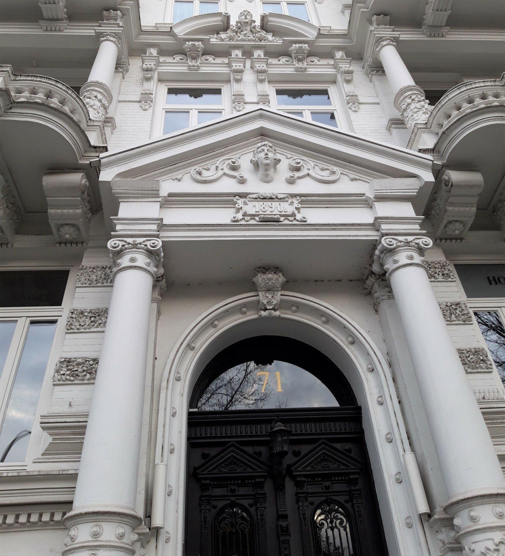 Üppig verzierte, weiß gestrichene Fassade eines Gründerzeitbaus, der bereits Jugendstil-Elemente enthält. Hausnummer 71steht auf dem Glasfenster über der dunkelbraunen Holztür.