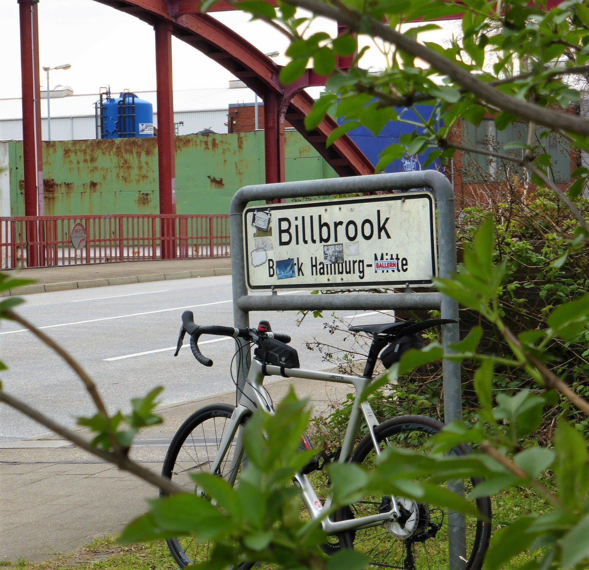 Im Hintergrund zeichnen sich rostrote Eisenbögen einer Brücke ab. Im Vordergrund zu sehen ist das Schild, das den Beginn des Stadtteils Billbrook markiert. Daran lehnt das Rennrad des RadelndenReporters.